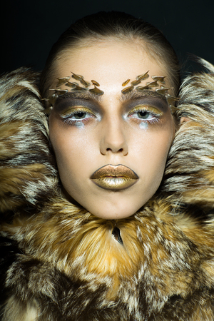 fur: Closeup portrait of one beautiful wild young woman with bright golden animal monkey makeup with thorns on face in fur coat in studio, vertical picture Stock Photo