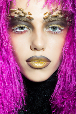 animal hair: Closeup portrait of one beautiful wild young woman with bright golden animal monkey makeup with thorns on face in fur violet wig in studio, vertical picture Stock Photo