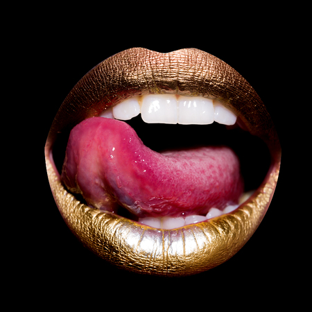 licking tongue: Closeup view of sexual beautiful female open golden lips with licking tongue and white teeth isolated on black background, square picture Stock Photo
