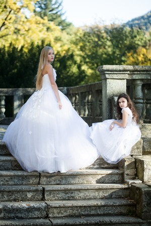sumptuous: Beautiful blonde bride in sumptuous lush white dress with brunette curly little girl in nice dress posing on stone stairs with handrail background in autumn park, vertical photo Stock Photo
