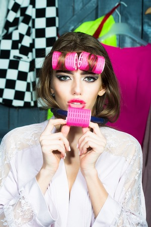 haircurlers: Closeup of one beautiful young fashionable housewife woman in dressing gown with hair-rollers on head and near mouth standing in wardrobe among many bright clothes, vertical picture