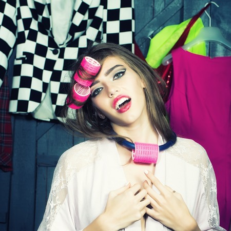 haircurlers: Closeup of one beautiful young fashionable emotional woman in dressing gown with hair-rollers on head standing in wardrobe among many bright clothes, square picture Stock Photo