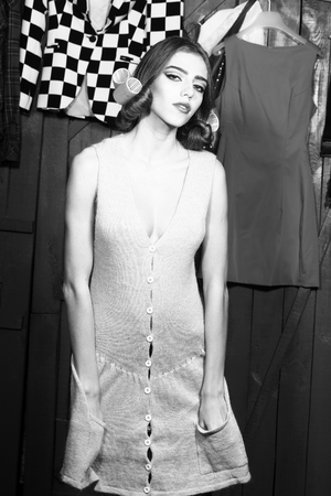 haircurlers: Closeup of one beautiful sensual young fashionable woman in knitted dress with hair-rollers on head standing in wardrobe among many bright clothes black and white, vertical picture