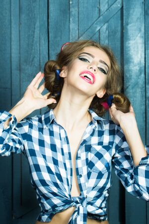 haircurlers: One beautiful sexy young stylish woman in checkered shirt and skirt with hair-rollers on head standing indoor on wooden wall stuio background, vertical picture