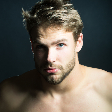 Closeup view portrait of one handsome young muscular macho man with short hair chest abd beautiful body standing in studio on black backdrop, square picture