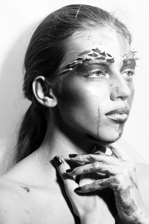 animal eye: Closeup portrait of one beautiful sexy wild young woman with bright animal makeup with thorns on face in studio black and white, vertical picture