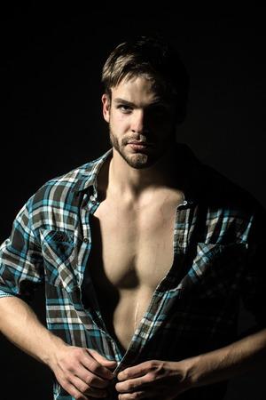 nackter junge: Nahaufnahme Porträt eines gut aussehend ernste junge sexy stilvollen Mann mit schönen muskulösen Brust in karierten Hemd vorwärts im Studio auf schwarzem Hintergrund, vertikale Bild Lizenzfreie Bilder