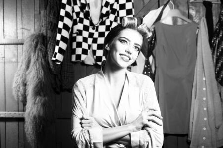 haircurlers: Closeup view of one beautiful young smiling housewife woman in dressing gown with hair-rollers on head standing in wardrobe among many bright clothes black and white, horizontal picture Stock Photo