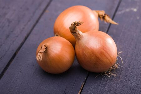 poignant: Glossy beautiful rustic organic sweet yellow onions shallot vegetables full of natural vitamins and nutrients for healthy diet on dark wooden background closeup, horizontal picture