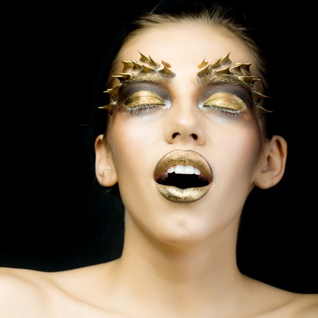 animal eye: Closeup portrait of one beautiful sexy wild young woman with bright golden animal makeup with thorns on face in studio on black background, square picture Stock Photo