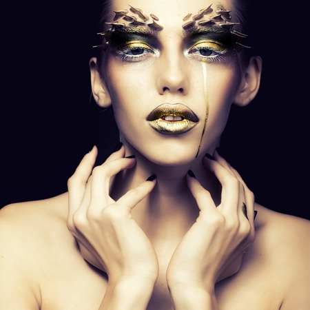 black makeup: Closeup portrait of one beautiful sexy wild young woman with bright golden animal makeup with thorns on face in studio on black background, square picture Stock Photo