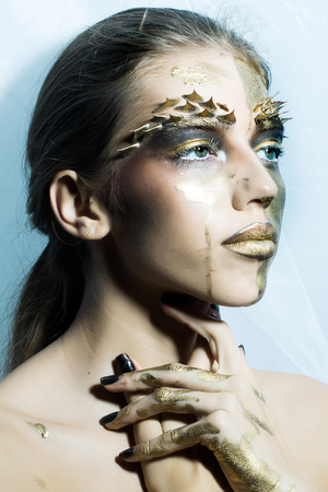 animal eye: Closeup portrait of one beautiful sexy wild young woman with bright golden animal makeup with thorns on face in studio on white background, vertical picture