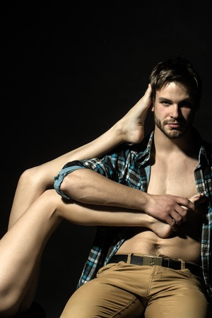One handsome confident young man in beige jeans and checkered shirt sitting in studio holding straight beautiful long female legs on black background, vertical picture