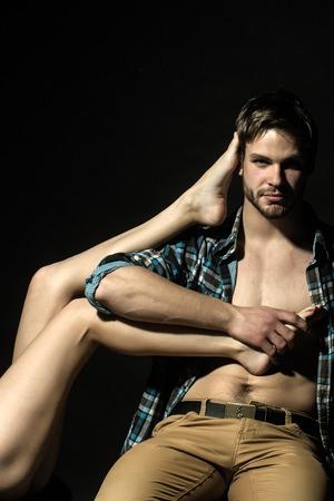 Un beau confiant jeune homme en jeans et chemise à carreaux beige assis en studio tenant droite belles longues jambes féminines sur fond noir, verticale de l'image