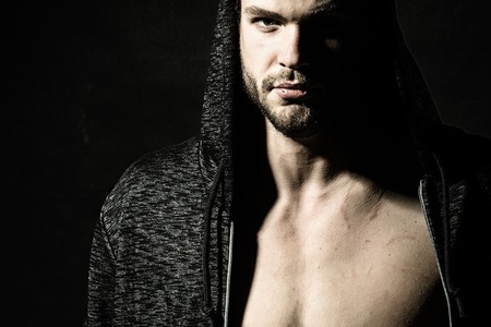 bare breast: Portrait of one handsome confident serious young sexy man with strong body and muscular bare chest in jacket with hood looking worward in studio on black background, horizontal picture Stock Photo