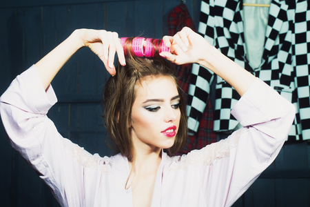 haircurlers: Closeup view of one beautiful young glamour housewife woman in dressing gown with hair-rollers on head standing in wardrobe among many bright clothes with raised hands, horizontal picture Stock Photo