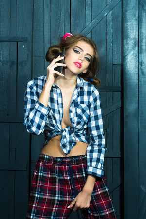 haircurlers: One smiling sexy young stylish woman in checkered shirt with hair-rollers on head with mobile phone standing in studio on wooden wall backdrop, vertical picture