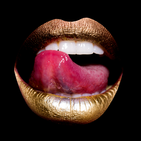 Closeup view of sexual beautiful female open golden lips with licking tongue and white teeth isolated on black background, square picture Banco de Imagens