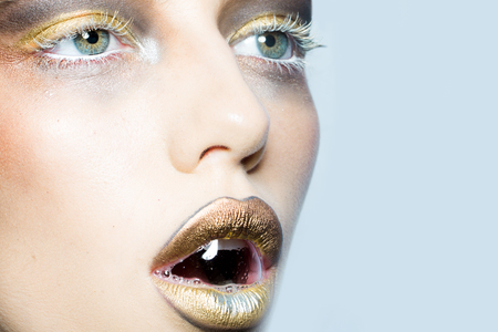 animal eye: Closeup portrait of one beautiful sexy wild young woman with bright golden animal makeup with bubble in open mouth in studio on white background, horizontal picture Stock Photo