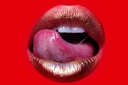 sexy young girl: Closeup view of sexual beautiful female open golden lips with licking tongue isolated on red background, horizontal picture Stock Photo