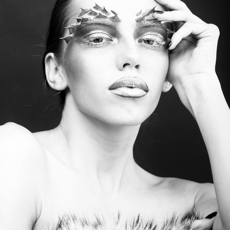 animal sexy: Closeup portrait of one beautiful sexy wild young woman with bright animal makeup with thorns on face in studio black and white, square picture