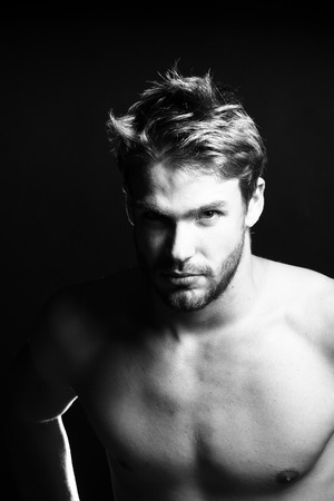 Closeup view portrait of one handsome young muscular naked sexy macho man with short hair bare chest abd beautiful body standing in studio black and white, vertical picture