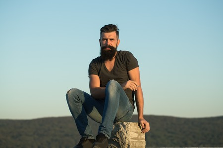 Closeup view of one handsome man with long lush dark haired beard in green shirt sitting on stone outdoor in sunset on blue sky background, horizontal picture