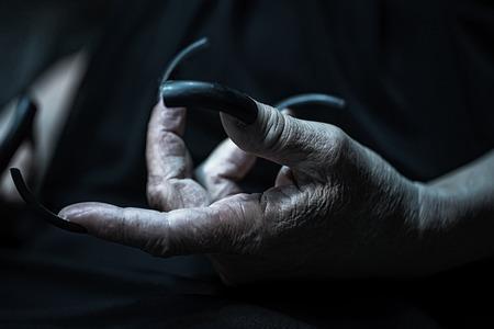 unas largas: Foto de primer plano de la mano femenina de la mujer mayor con la piel arrugada de edad y las u�as largas en pico de loro pulido blanco sobre fondo borroso oscuro y negro, cuadro horizontal