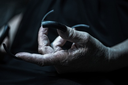 Photo closeup of female hand of old woman with aged wrinkled skin and polished long parrot-beak fingernails black and white on dark blurred background, horizontal picture Standard-Bild