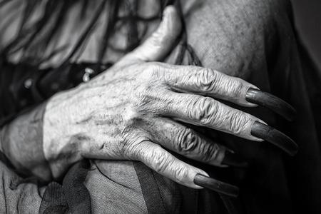 unas largas: Foto de primer plano de la mano femenina de la mujer mayor con la piel arrugada de edad y las u�as largas en pico de loro pulidas sosteniendo el brazo de tul blanco sobre fondo borrosa oscuro y negro, cuadro horizontal