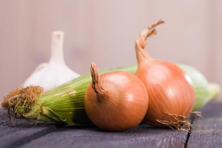 espiga de trigo: Conjunto de veh�culos apetitosos rurales frescas maduras dulce de ma�z o�do oro cebollas vibrantes y picante de ajo ingredientes org�nicos brillantes para el estudio de la comida sana sobre fondo claro primer plano, horizontal Foto de archivo
