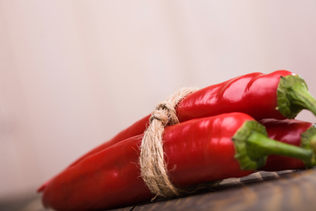 savour: Three ripe raw natural bright red burning peppers cayenne vegetable with pungent savour tied with rope laying on wooden table on light background studio closeup, horizontal picture