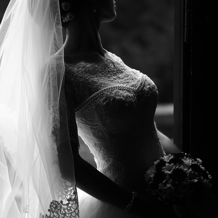 Photo closeup of beautiful young bride in ornamental wedding lace dress long veil holding elegant bouquet of fresh flowers for bridal ceremony black and white on grey background, square picture Stock Photo