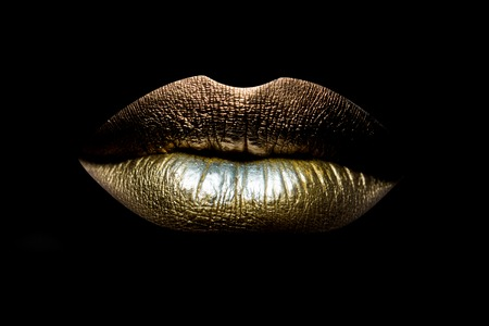 girl face close up: Closeup view of sexual beautiful female closed golden lips isolated on black background, horizontal picture Stock Photo