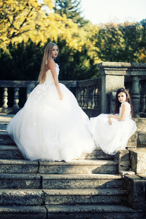 Young bride with white long hair in luxury lush white dress with curly younger sister in nice dress posing on stone stairs with handrail background outdoor, vertical photo