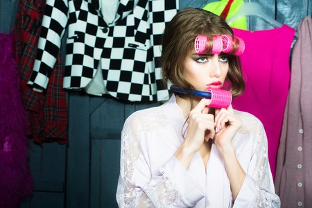 haircurlers: Closeup of one beautiful young fashionable housewife woman in dressing gown with hair-rollers on head and near mouth standing in wardrobe among many bright clothes, horizontal picture
