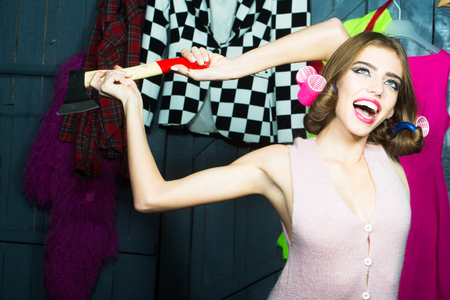 haircurlers: One beautiful smiling emotional young fashionable woman in knitted dress with hair-rollers on head holding sharp axe in hands standing in wardrobe among many bright clothes, horizontal picture Stock Photo