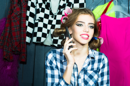 haircurlers: One smiling sexy young stylish woman in checkered shirt with hair-rollers on head with mobile phone standing in wardrobe among many bright clothes, horizontal picture