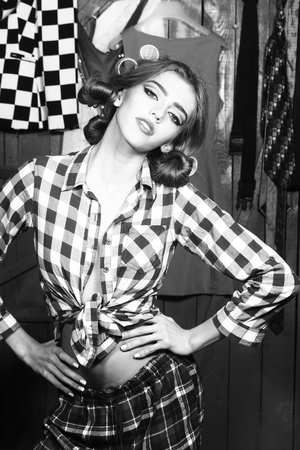 haircurlers: One beautiful sexy young stylish woman in checkered shirt and skirt with hair-rollers on head standing in wardrobe among many bright clothes black and white, vertical picture Stock Photo