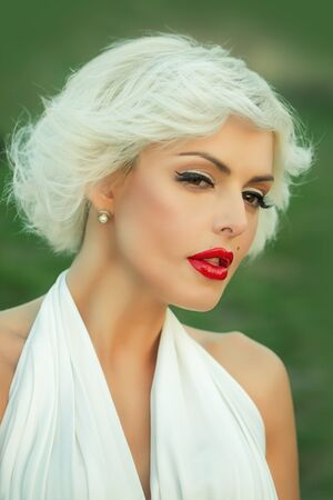 monroe: Closeup portrait of one attractive sensual dreaming young retro woman with blonde hair red lips in white dress in monroe style outdoor on natural background, vertical picture Stock Photo