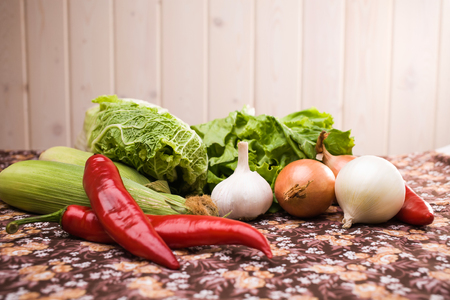 nutriments: Organic natural ingredients with vitamins and nutriments in harvest summer season variety of raw fresh vegetables laying on floral tablecloth on light background indoor closeup copyspace, horizontal Stock Photo