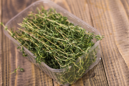 potherb: Fragrant eating rosemary pot-herb healthy organic ingredient spiciness with piquant flavour in plastic food box on wooden background studio closeup, horizontal picture