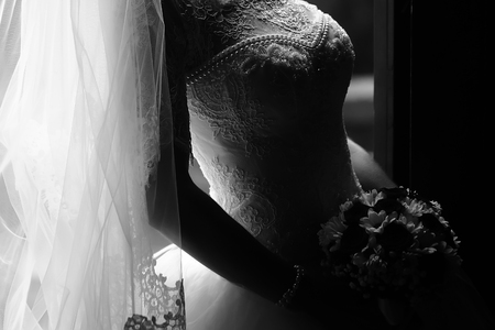 Fotoclose-up van mooie jonge bruid in sier de lange sluier die van de huwelijkskant elegant boeket van verse bloemen voor bruids ceremonie zwart-wit houden op grijze achtergrond, horizontaal beeld houden