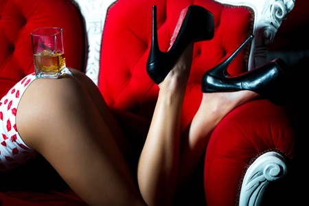 Sexual beautiful female buttocks and legs of young woman with straight slim body flexible body in underwear with kiss pring and high heeled shoes with glass of alcoholic beverage of brandy or whisky