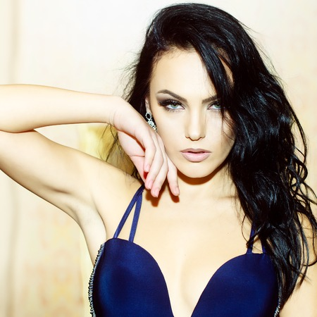 sexuel: Portrait d'une belle jeune femme brune aux cheveux bouclés sexuelle corps droit mince et maquillage lumineux en bleu robe élégante debout image intérieure, carré