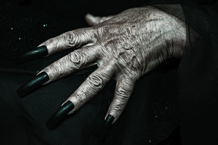 puckered: Photo closeup of female hand of old woman with aged wrinkled skin and polished long parrot-beak fingernails black and white lying on dark mourning blurred tulle background, horizontal picture