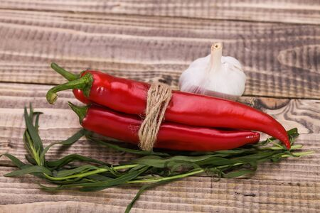 poignant: Group of ingredients condiments bunch of hot chili peppers branches of eating herb aroma garlic vegetable with spicy poignant flavour for culinary closeup on wooden background closeup, horizontal Stock Photo
