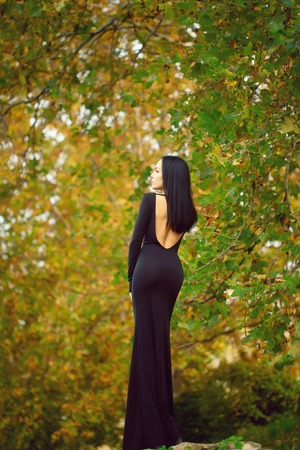 Back view of one beautiful sensual sexy slim brunette pensive woman standing in autumn forest outdoor in long black dress on natural background, vertical picture Stock Photo
