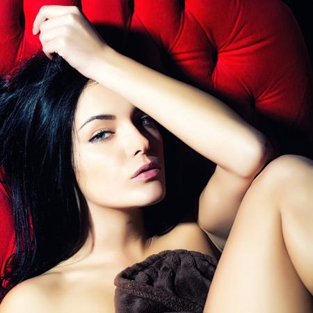 mujeres jovenes desnudas: Una morena desnuda niña muy sexual con cuerpo delgado hermoso y pelo largo que se sienta en el estudio de interior en el sofá rojo clásico deseando en el fondo brillante, imagen cuadrada