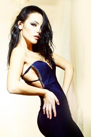 ojos negros: Una joven morena hermosa mujer sexual con el pelo rizado delgado cuerpo recto y maquillaje brillante en elegante vestido azul que se coloca la imagen en interiores, vertical
